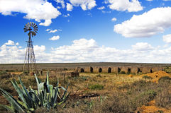 Windmill and Hay Bales. Water pumping windmill and hay bales in rural australia, blue sky and white clouds in rural Australia Stock Image