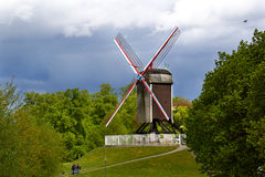 A windmill on a on a hill in Bruges. Surrunded by trees stock image