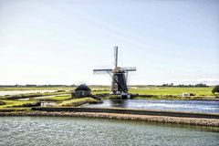 Windmill in Holland. A windmill is a machine that converts the energy of wind into rotational energy by means of vanes called sails or blades Stock Photo