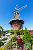 Windmill in Holland Michigan at Springtime. An authentic wooden windmill from the Netherlands stands among tulips and other vegetation on Windmill Island in royalty free stock image