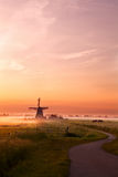 Windmill and horses on pasture at sunrise Royalty Free Stock Photography