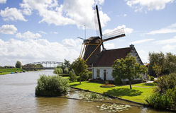 Windmill, house and bridge at the waterside Stock Photos