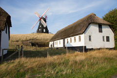Windmill between houses. Black Windmill on a hill between houses Royalty Free Stock Images