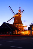 Windmill illuminated at night. Exterior of windmill illuminated at night with road in foreground royalty free stock images