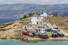 A windmill with its sails on in Koufonsion Greece with winter stored boats in front Stock Photography