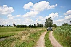 Windmill at Kinderdijk. A vintage automobile making its way along a dirt road at Kinderdijk Stock Photography