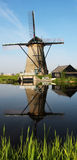 Windmill in Kinderdijk. Scenic view of windmill of Kinderdijk reflecting in canal in foreground, Netherlands Stock Image