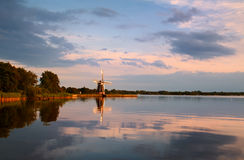 Windmill on lake at sunset Stock Photography