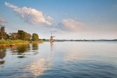 Windmill by large lake and blue sky Stock Image
