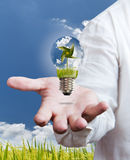Windmill in a light bulb on hand Stock Photography