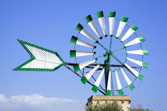 Windmill in Majorca. Isolated white and green windmill in Majorca with a blue sky as background Stock Photo