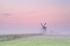 Windmill on meadow in morning fog Royalty Free Stock Photos