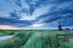Windmill on meadow at sunrise Stock Photos