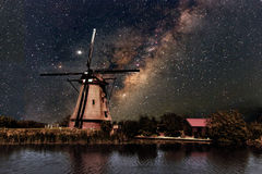 A Windmill and the milky way. Milkey way shine on a beautiful Dutch windmill at Kinderdijk in Netherlands stock photo