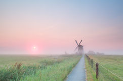 Windmill on misty Dutch farmland Royalty Free Stock Photos