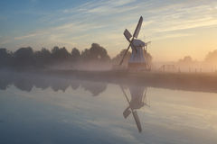 Windmill in morning sunshine reflected in river Royalty Free Stock Photography