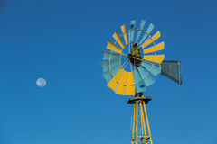 Windmill in motion against dark blue clear sky on sunny day Stock Image