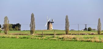 Windmill in a n English rural landscape with fields of crops Royalty Free Stock Photography