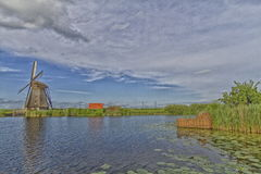 Windmill near the water canal in Netherlands Stock Photos