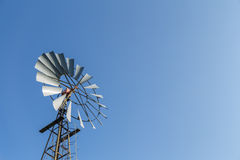 Windmill nestled in a blue sky. A old windmill used for pumping water nestled in a blue sky stock photo