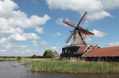 Windmill in The Netherlands. Windmill with water canal in the foreground. Sky with clouds. The windmill is still in operation and power an industrial lumber saw Royalty Free Stock Photo