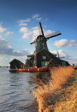 Windmill at Netherlands. Windmill at  Zaanstad, Netherlands. With boat and river in foreground Royalty Free Stock Image