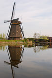 A windmill next to a house in kinderdijk with beautiful water reflection Stock Photos