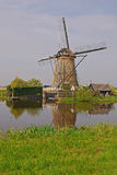 A windmill next to a house in kinderdijk with beautiful weather & water reflection stock photo