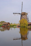 A windmill next to a house and tree in kinderdijk with beautiful water reflection Royalty Free Stock Image