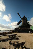 Windmill next to lake. Windmill and wooden tools and benches next to lake in Zaanse Schans, Netherlands. Typical symbol of culture in the Netherlands Royalty Free Stock Image