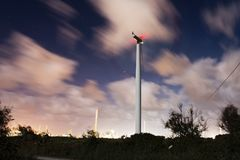 Windmill at night and cloudy sky. Windmill in the night with industries and cloudy sky. Long exposure at night Stock Photos