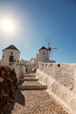 Windmill in Oia, Santorini. Shot at sunrise. Vertical shot, sun on background Royalty Free Stock Image