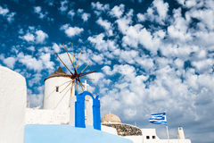 Windmill in Oia town. White architecture on Santorini island, Greece. Beautiful cloudscape Stock Image