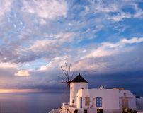 Windmill in Oia village on Santorini island, Greece, at sunset Royalty Free Stock Photo