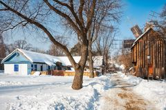 A Windmill and an old cottage covered in snow at the Village Museum, Bucharest stock image