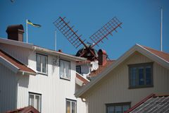 Windmill over rooftops. Windmill over the rooftops in a fisherman village on the Swedish westcoast stock image