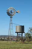 Windmill in paddock. Windmill and tankstand in paddock, Queensland, Australia. Windmills are commonly used for pumping water from bores or dams to troughs for Royalty Free Stock Photo