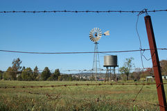 Windmill in paddock. Windmill and tankstand in paddock, Queensland, Australia. Windmills are commonly used for pumping water from bores or dams to troughs for Stock Photography