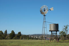 Windmill in paddock. Windmill and tankstand in paddock, Queensland, Australia. Windmills are commonly used for pumping water from bores or dams to troughs for Stock Images