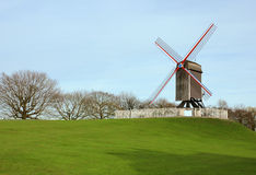 Windmill in the park in Bruges, Belgium. Windmill in Bruges, Belgium shot of green grass and blue sky background Royalty Free Stock Photos