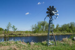 Windmill beside pond Stock Photography