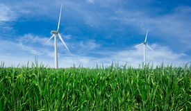 Windmill power generator. Windmill power generator on green grass and blue sky Stock Photo