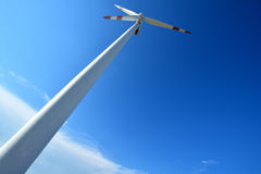 Windmill power generator. Under blue sky, shown as energy industry concept Stock Image