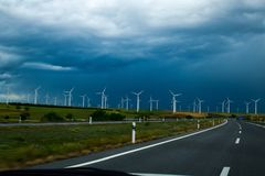 Windmill power plant. Electricity generation close to road. Environmentally friendly electricity production stock photos
