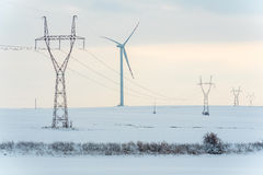 Windmill and powerlines on the field in winter Royalty Free Stock Photos