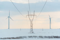 Windmill and powerlines on the field in winter Stock Photography