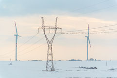 Windmill and powerlines on the field in winter Stock Photo