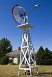 Windmill and Pump. Old-fashioned windmill and pump stand near a farmhouse under a cloudless sky Royalty Free Stock Images