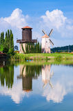 Windmill reflect water. Windmill reflection on the water with blue sky background Royalty Free Stock Images