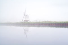 Windmill reflected in river and dense fog Royalty Free Stock Image